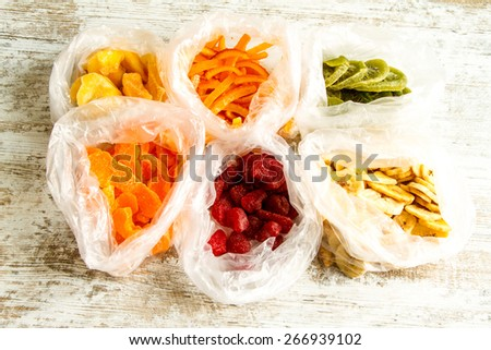Selection of colorful dried fruits in bags background  - stock photo