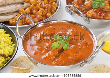 Selection of curry dishes with rogan josh, pillau rice,chana dhal,chicken jalfrezi and poppadums. - stock photo