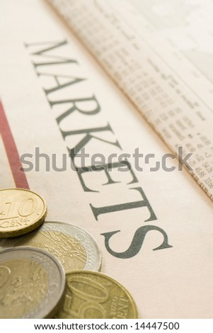 selection of euro coins on paper marked Markets - stock photo