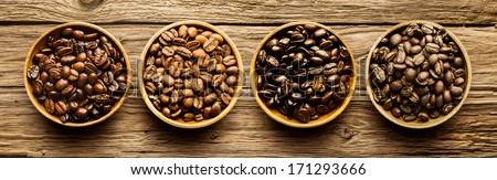 Selection of four different fresh dried roasted coffee beans in individual containers arranged in a line viewed from above on a textured driftwood background - stock photo