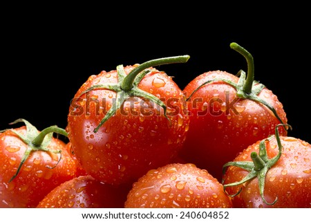 Selection of fresh, ripe red tomatoes framed against a black background for placement of copy. - stock photo