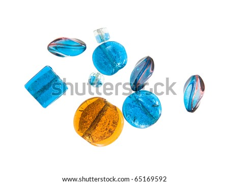 selection of glass and resin beads in blue with one in contrasting complementary orange-yellow; isolated on white background; - stock photo