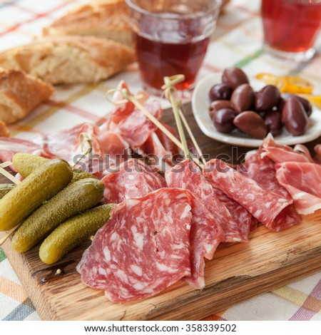 Selection of hams and salami on vintage wooden cutting board - stock photo