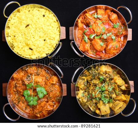 Selection of Indian chicken and vegetable curries with rice. - stock photo