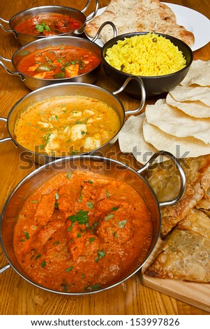 Selection of indian curries with pilau rice, naan bread, poppadoms and samosas a popular buffet choice - stock photo