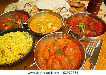 Selection of indian food with pilau rice, naan bread, poppadoms and samosas a popular choice for eating out in european countries - stock photo