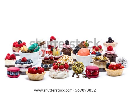 Selection of miniature cakes, macarons, cupcakes and treats, isolated