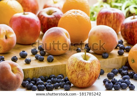 Selection of mixed fruit filling the frame making a nice food background. Apples,Oranges, Blueberries, and Peaches, with a Shallow depth of field. - stock photo