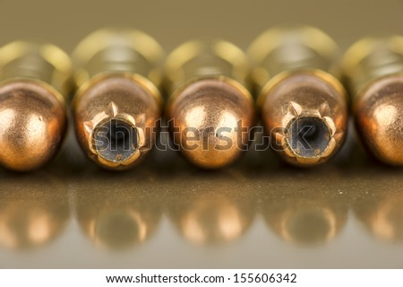 Selection of 9mm and .380 bullets on gold plastic - stock photo