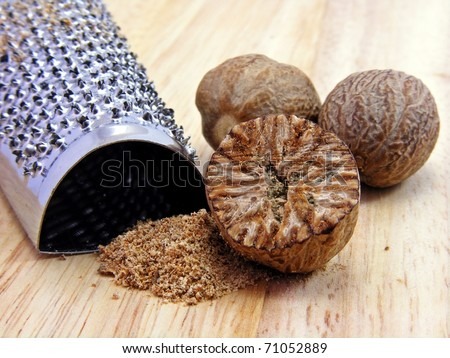 Selection of nutmeg with stainless steel hand grater - stock photo