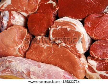 Selection of various cuts and portions of fresh succulent raw uncooked red meat displayed ready for cooking - stock photo