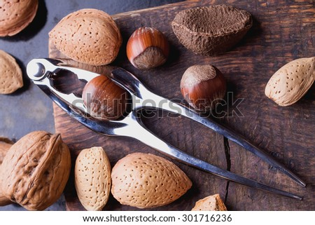 Selection of various nuts: almonds, Brazilian, walnuts on tiny vintage wooden board, black background - stock photo