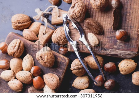 Selection of various nuts: almonds, Brazilian, walnuts on tiny vintage wooden boards, black background, top view - stock photo