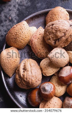 Selection of various nuts in the vintage ceramic plate, black background, top view
