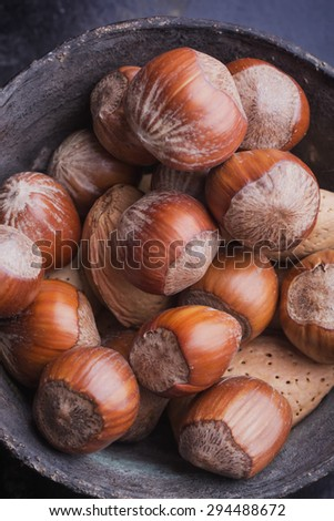 Selection of walnuts in the vintage copper chinese bowl, black background, top view - stock photo