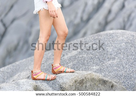 Selective focus at young girl leg walk on the grey hill during summer.