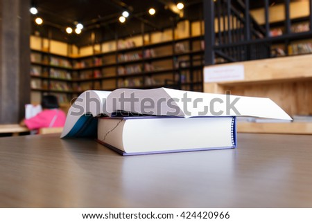 Selective focus books in public library and blurred book shelves. - stock photo