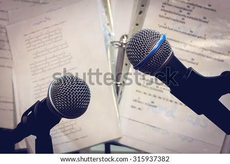 Selective focus both microphone on the blur lyric background vintage tone and vignetting. - stock photo