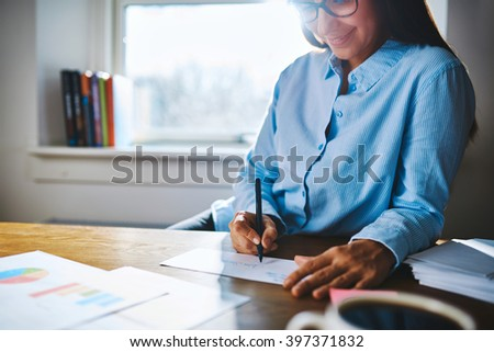 Selective focus close up of cheerful young self-employed woman wearing glasses and blue shirt at desk writing on form next to cup of coffee and booklets