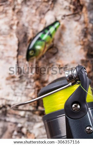 selective focus closeup fishing bait wobbler and reel with line on wooden background - stock photo
