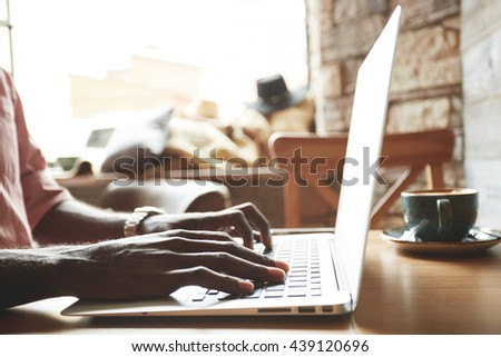 Selective focus. Cropped shot of African American freelancer keyboarding on laptop computer while working on new project at home. Black student looking for information for his diploma on the Internet - stock photo