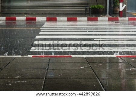 Selective focus , Crosswalk and red white footpath in rainy season - stock photo