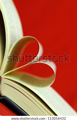 Selective focus image of book pages folded into a heart shape - stock photo