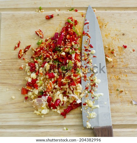 Selective focus image of chopped garlic with red and green hot chilli and a knife on a wooden board. - stock photo