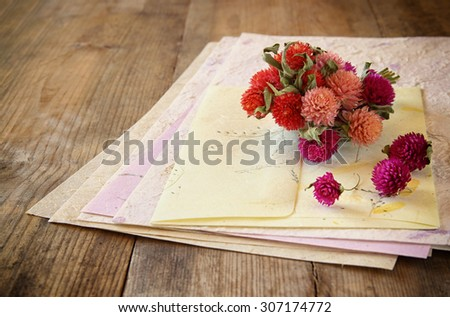selective focus image of dry flowers and hand made vintage letters paper on wooden table. retro filtered image