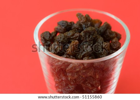 Selective focus image of raisins in a glass which are often in cereal products like muesli.