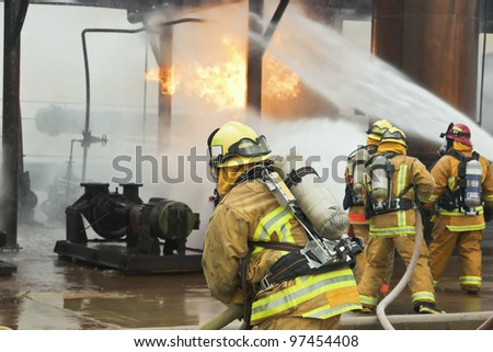 Selective focus is on the firefighter in the foreground.