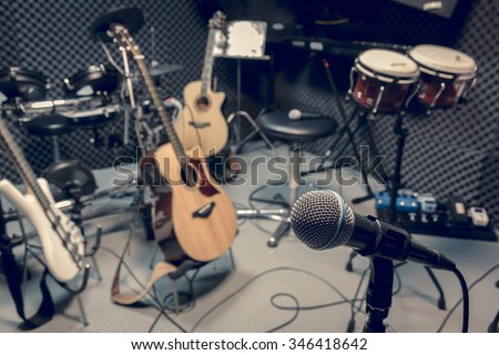 selective focus microphone and blur musical equipment guitar ,bass, drum piano background. - stock photo