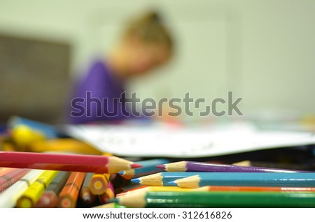 Selective focus of colour pencils in the foreground while a child, girl age 05,  drawing in the background. Horizontl (copy space) - stock photo