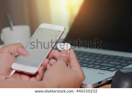 Selective focus of Hands holding hand holding earphone and screen of white smartphone device  on computer keyboard as technology and telecommunication concept.