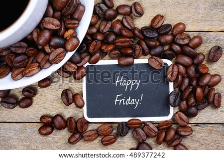 Selective focus of HAPPY FRIDAY! text written on the chalkboard, coffee beans and white cup on the wooden background.
