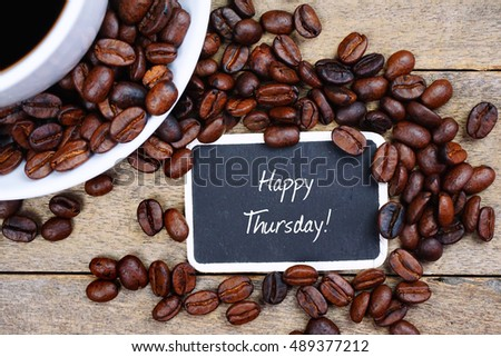 Selective focus of HAPPY THURSDAY! text written on the chalkboard, coffee beans and white cup on the wooden background.