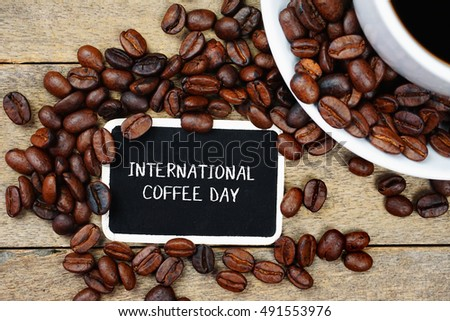 Selective focus of INTERNATIONAL COFFEE DAY text written on the chalkboard, coffee beans and white cup on the wooden background.