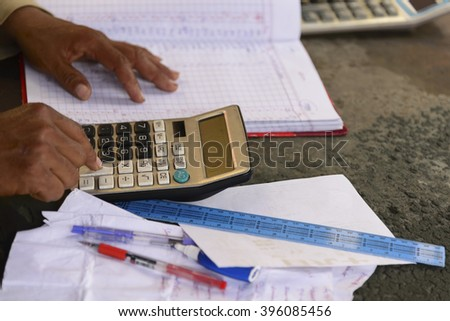 selective focus of Man work out accounts with paper ruler pen and calculator on old desk - stock photo