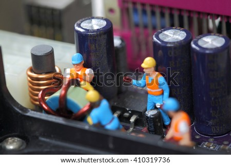Selective focus of miniature engineer and worker fixed and maintenance mainboard computer and use for business background. - stock photo