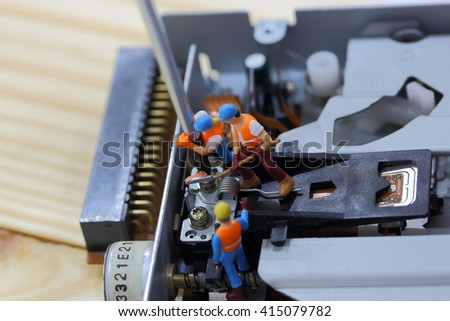 Selective focus of miniature engineer and worker fixed and repair cd rom of computer and use for business background. - stock photo