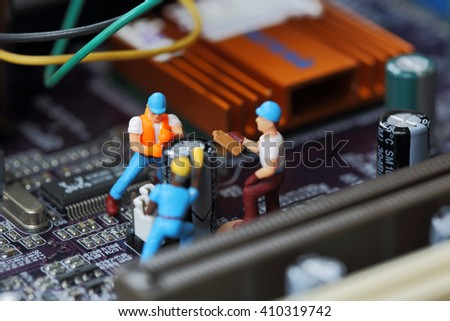 Selective focus of miniature engineer and worker fixed to remove chip and  mainboard computer and use for business background. - stock photo