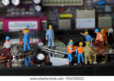 Selective focus of miniature engineer and worker maintenance hard disk and fixed problem hard disk of Personal computer (PC) on blurred mainboard background as business and industrial concept. - stock photo