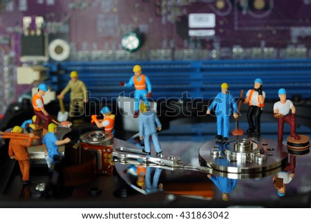 Selective focus of miniature engineer and worker, maintenance hard disk and fixed problem Harddisk (Hard disk) of Personal computer (PC) on blurred mainboard background as business industrial concept - stock photo