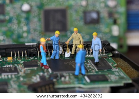 Selective focus of miniature engineer discuss and worker fixed problem on chips and computer mainboard as business and industrial concept. - stock photo