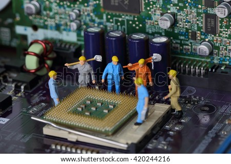 Selective focus of miniature engineer worker to fixed and repair Control Processing Unit (CPU) processor,  mainboard computer and use for industry background. - stock photo
