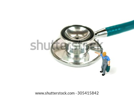 selective focus of miniature worker holding bag with green stethoscope on white background, abstract back ground to solution for Annual Health Check up. - stock photo
