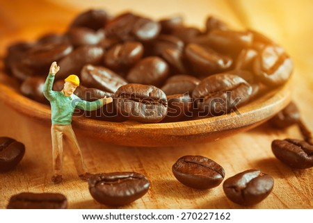 selective focus of miniature worker pointed at coffee bean on wooden spoon,love coffee concept. - stock photo
