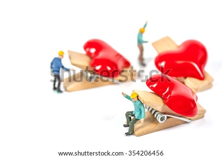 selective focus of miniature workers holding red heart shape wood clip isolated on white background , abstract background to valentine concept. - stock photo