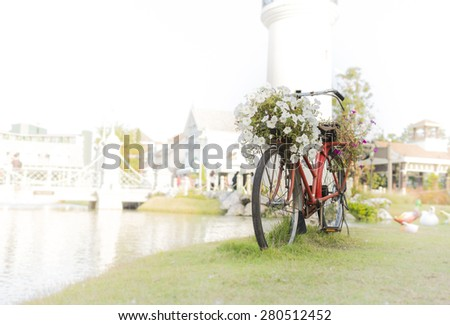 Selective focus of red vintage bicycle with basket and flowers - stock photo