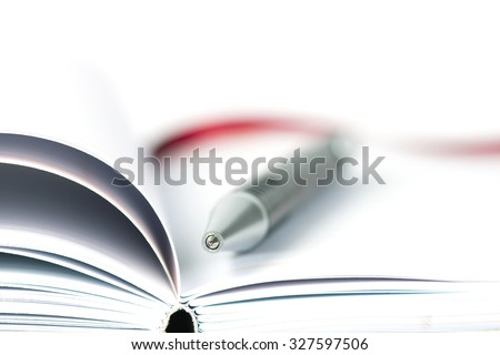 selective focus of the ball pen on opened lined diary book , extremely shallow DOF - stock photo